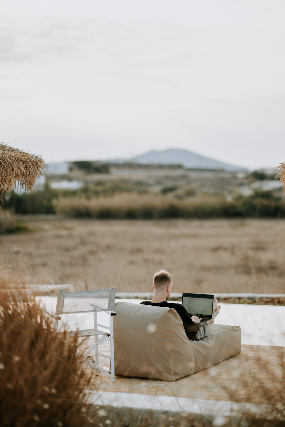 man using laptop on chaise lounge outdoor