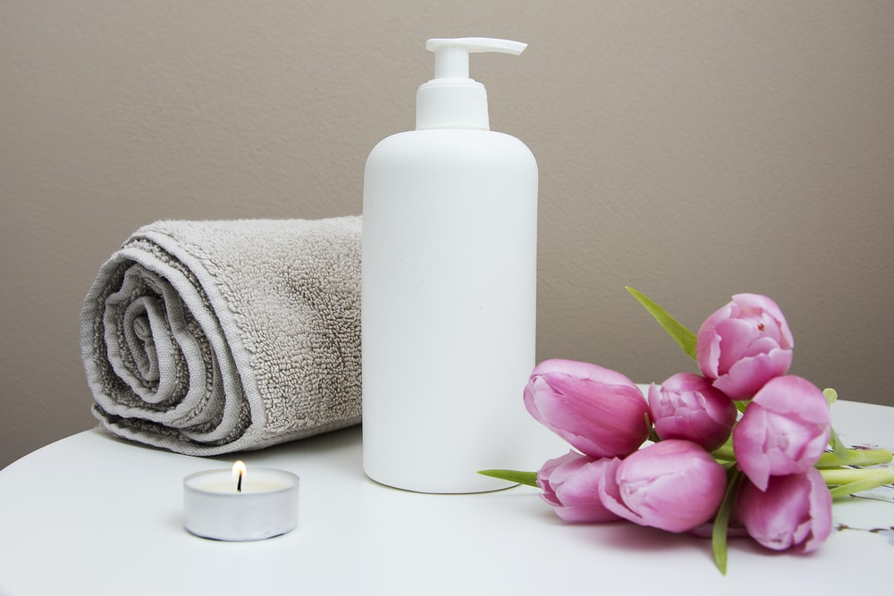 white plastic pump bottle beside pink tulips and gray towel