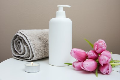 white plastic pump bottle beside pink tulips and gray towel beauty zoom background
