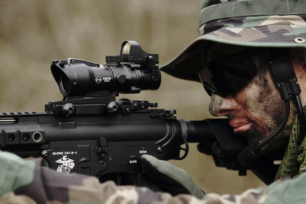 man in woodland camouflage uniform using sniper rifle