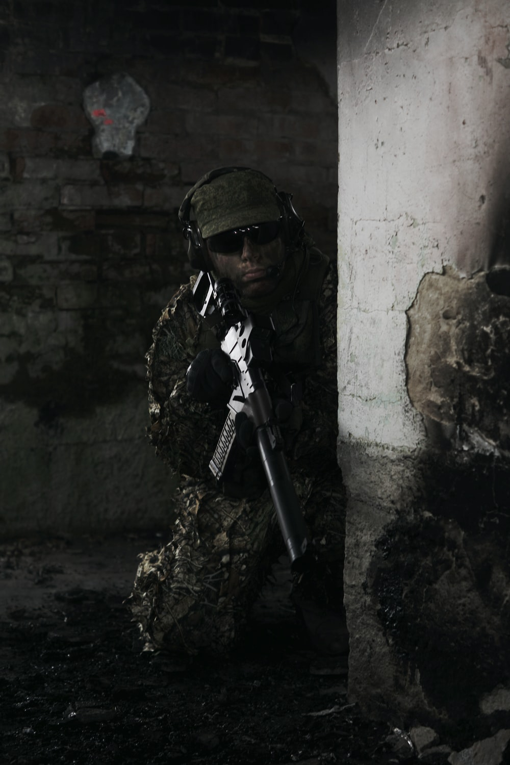 military personal in camouflage carrying rifle