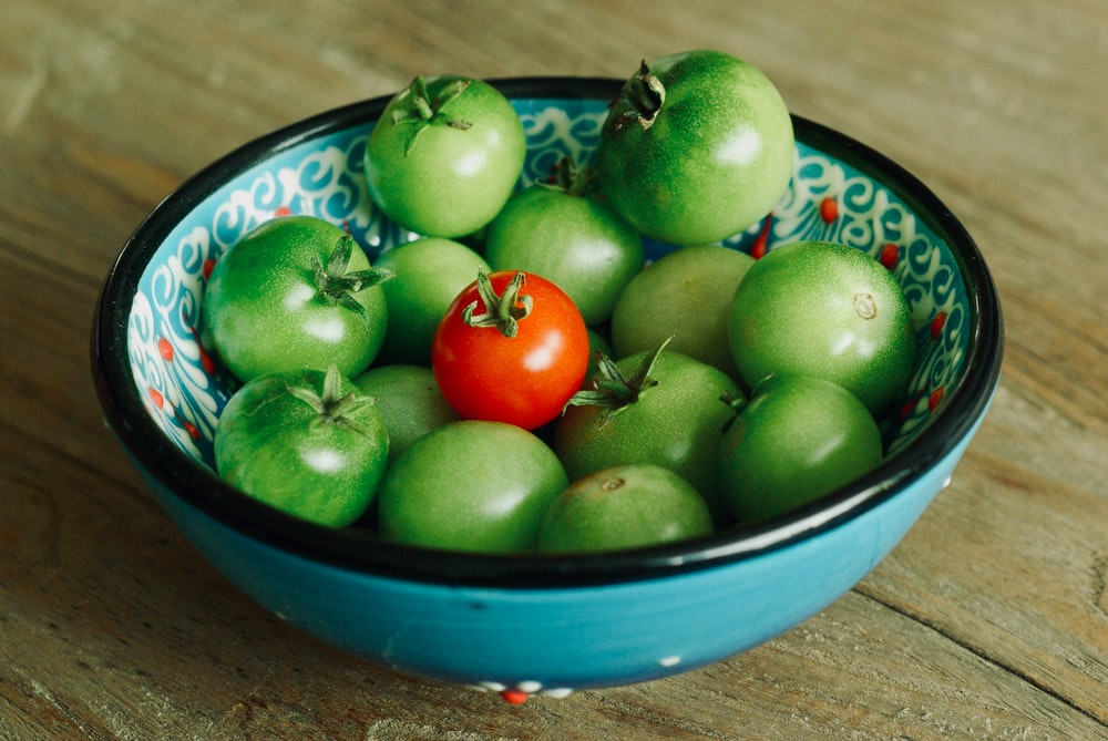 green and red tomatoes in bowl