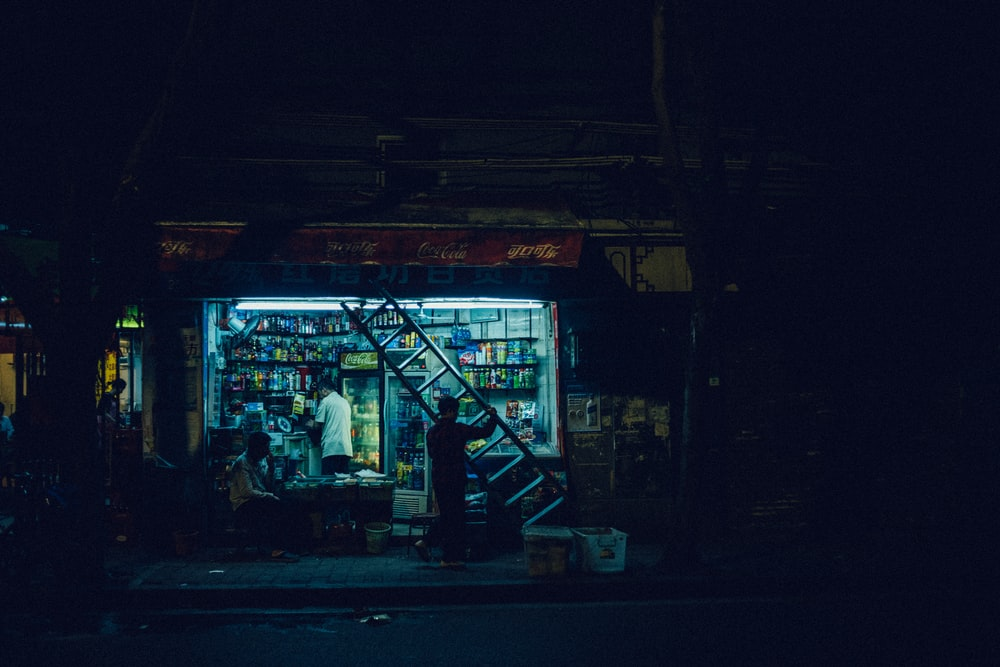 man carrying ladder in front open store at night