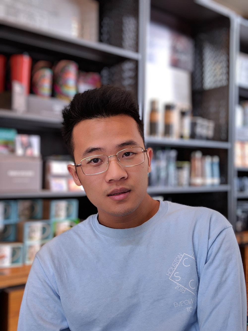 man wearing eyeglasses and blue shirt inside coffee shop