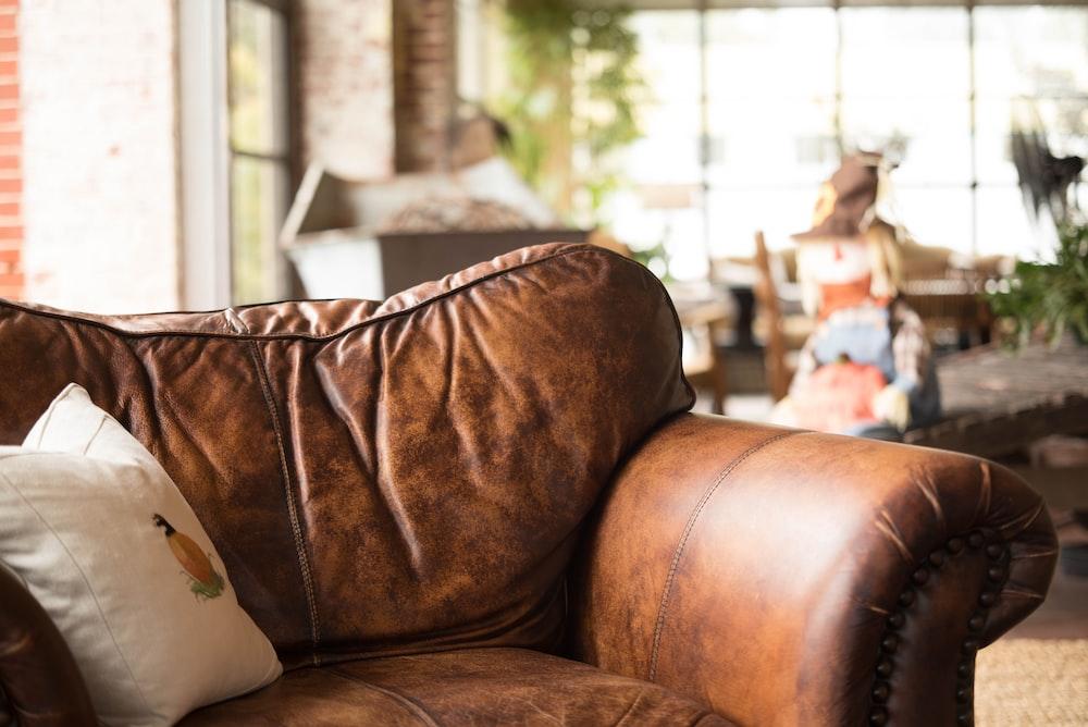 white throw pillow on brown leather armchair