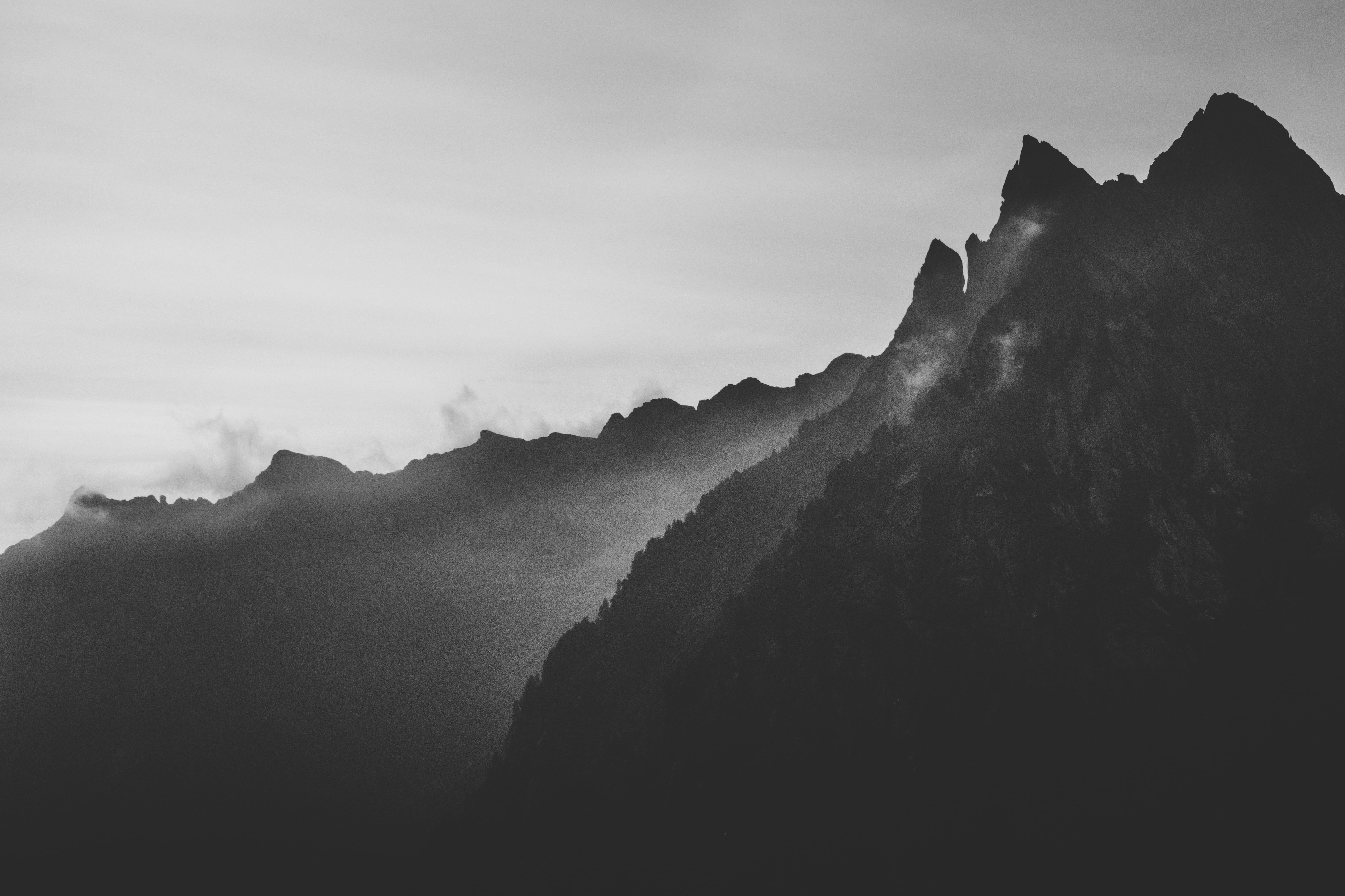 silhouette photography of mountain under fog