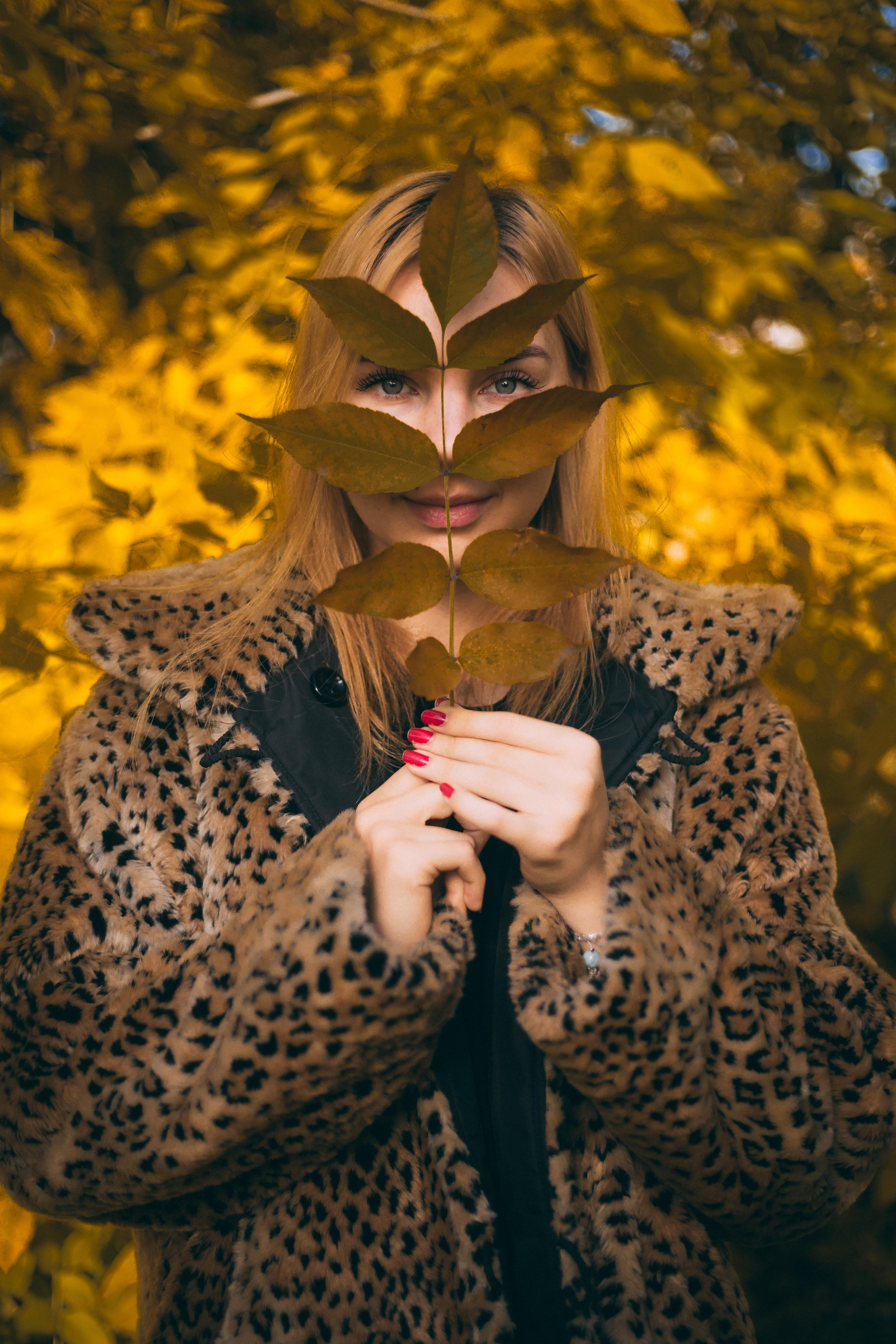 woman wearing leopard coat holding leaves