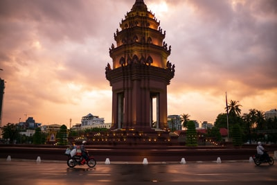person riding motorcycle near building cambodia zoom background