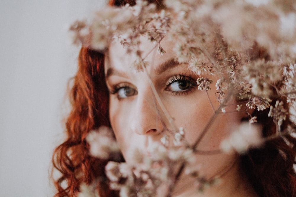selective focus photography of woman near plant