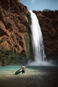 man in black shorts holding black and green buoy standing near waterfalls during daytime