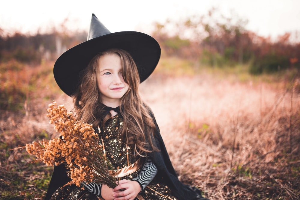 girl wearing black witch costume holding brown plant