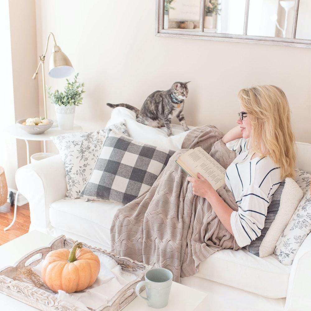 woman reading book on sofa