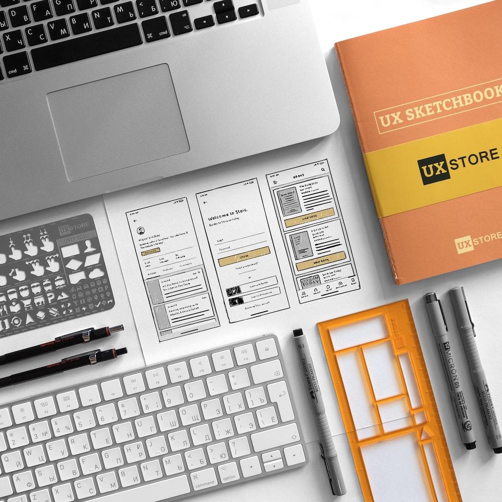 UX Sketchbook beside MacBook