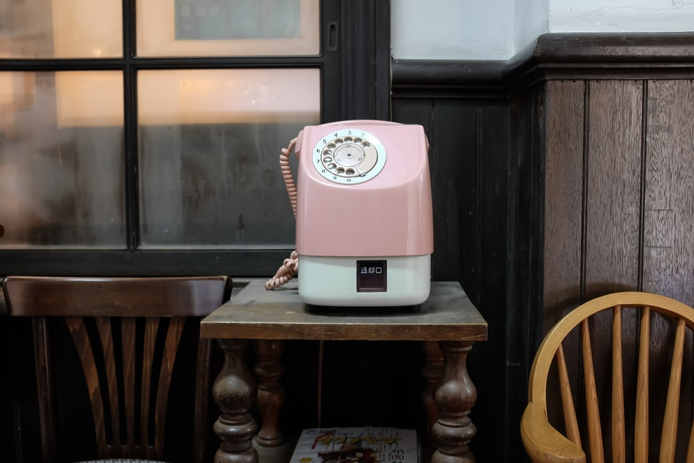 pink and white telephone on brown table
