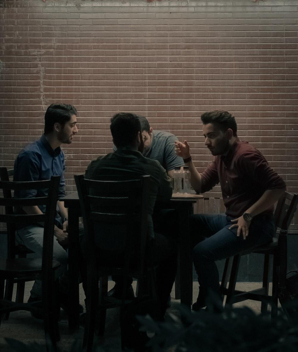 four men sitting beside table
