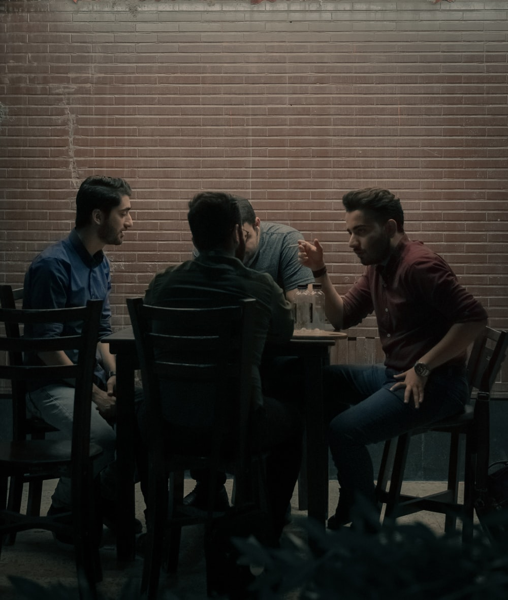 four men sitting beside table
