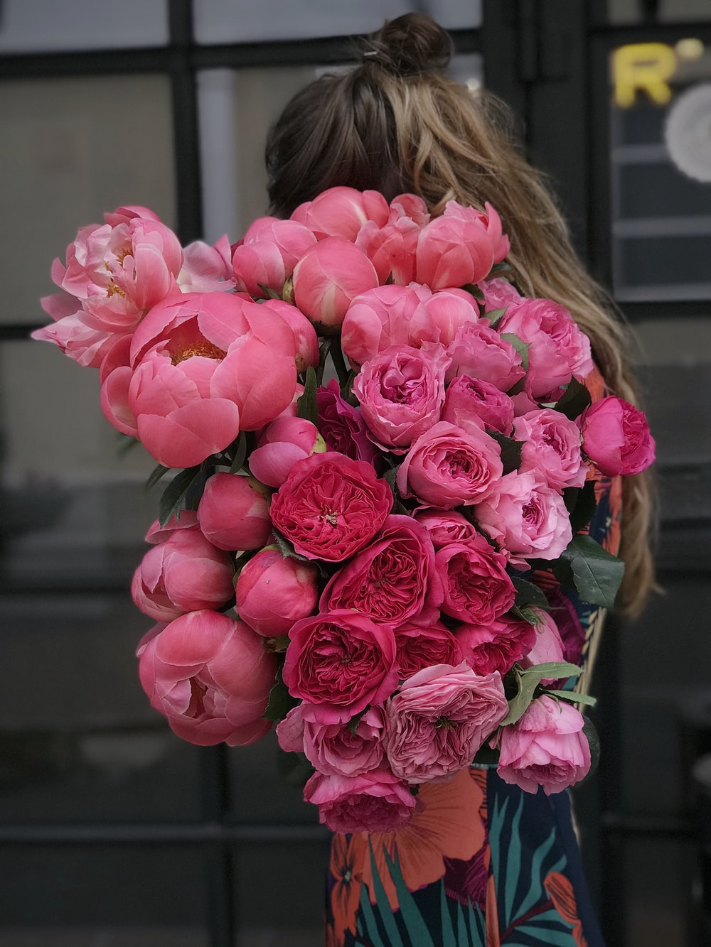 woman holding pink flowers