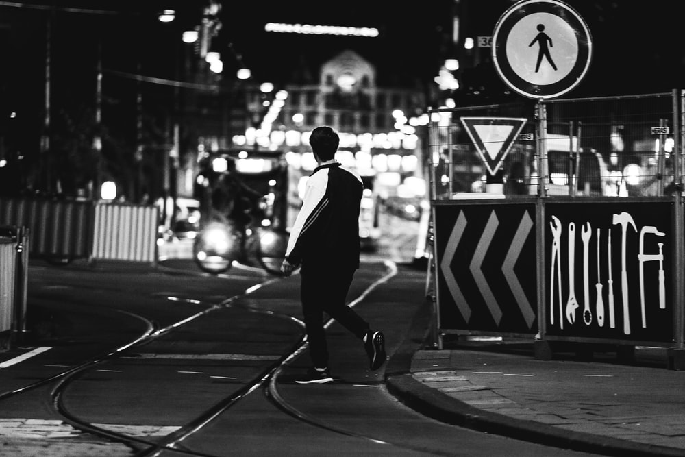 grayscale photography of man near road