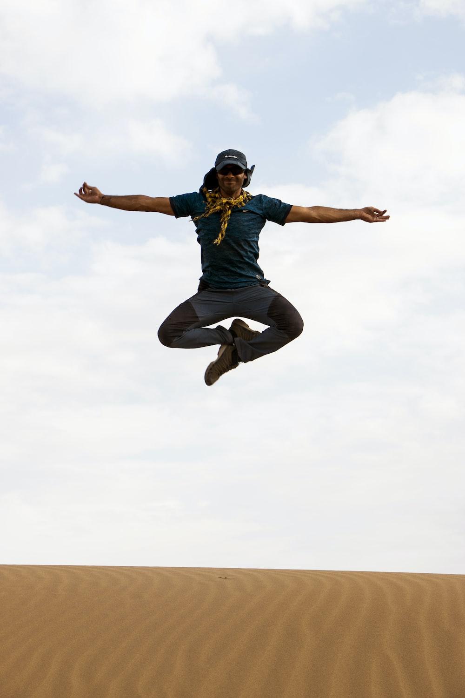 man jumping on sand during daytime