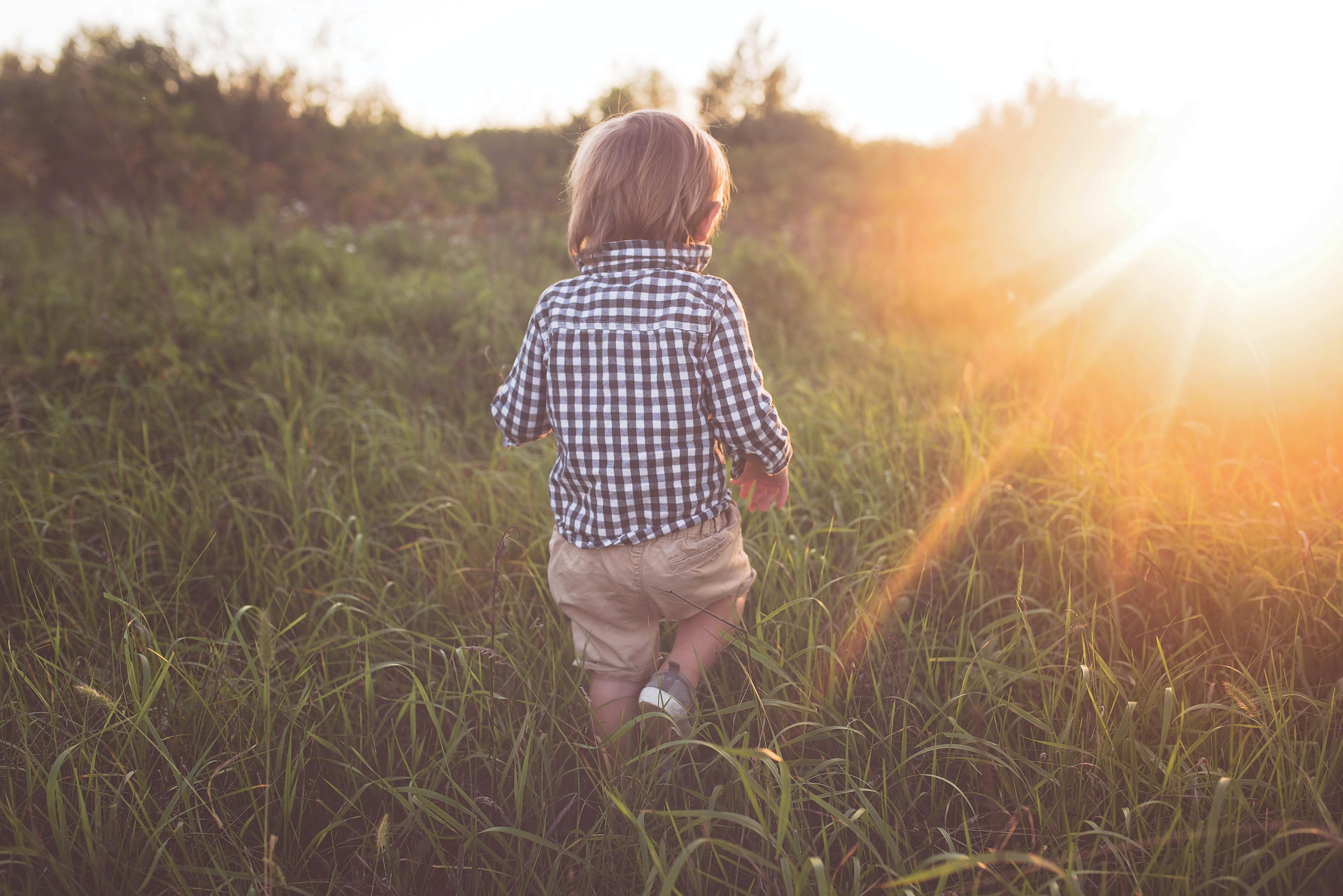 boy walking on grass field