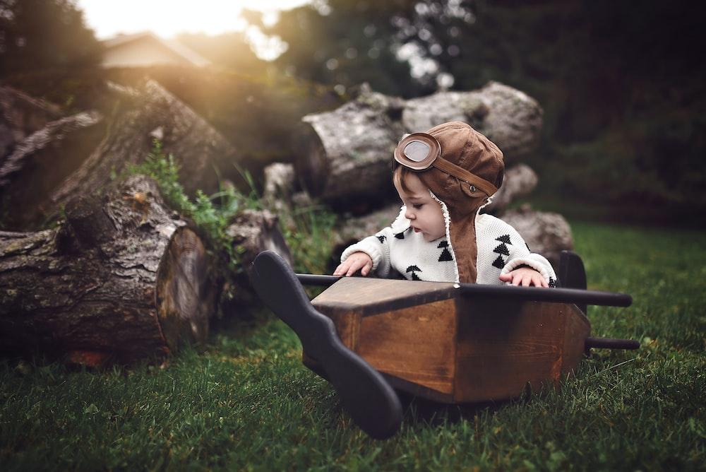toddler riding monoplane on green grass