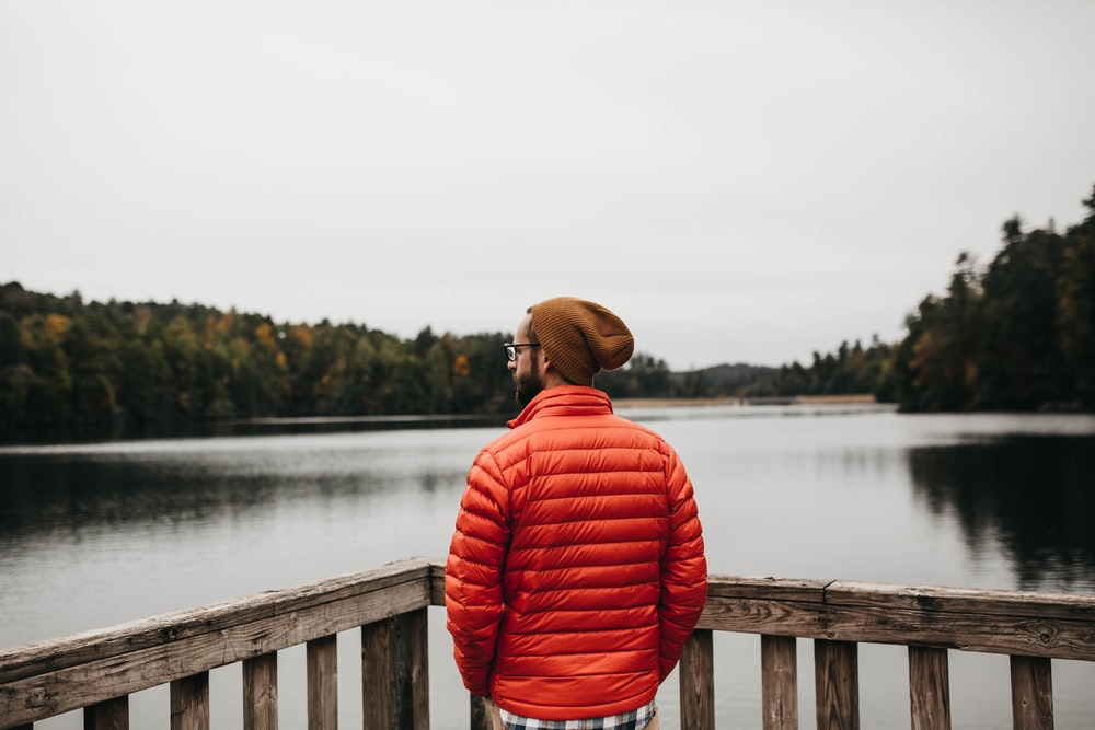 man standing near brown wooden balustrade facing body of water