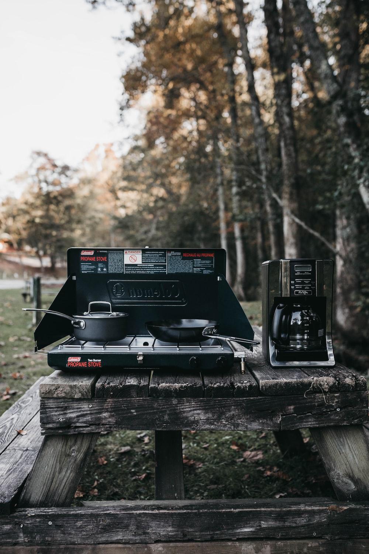 gray electric strove beside black coffeemaker near trees
