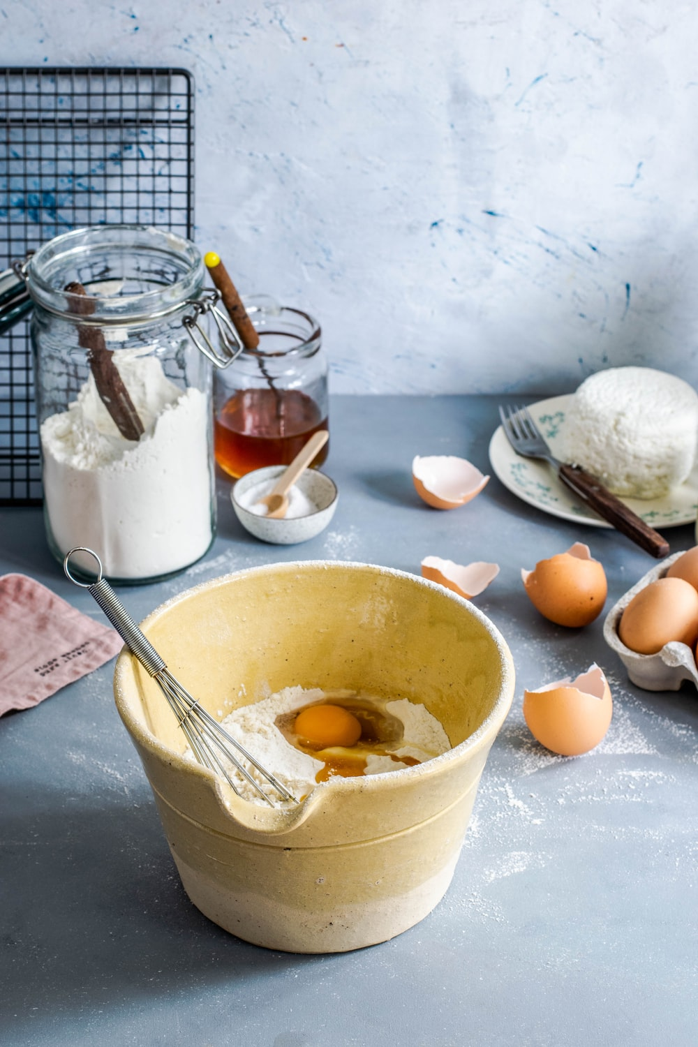brown mixing bowl with eggs and flour with whisk