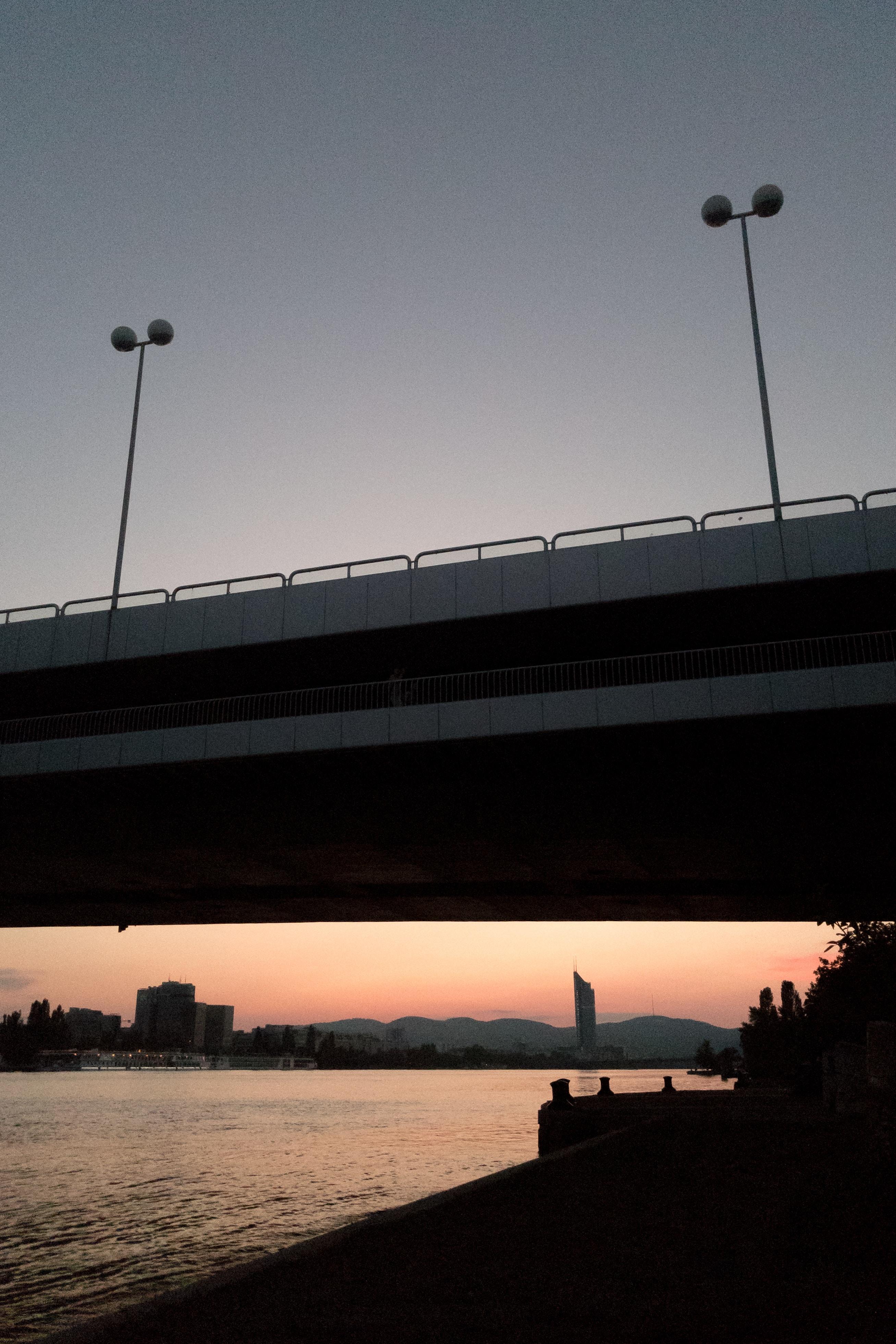 sunrise over bridge and body of water horizon
