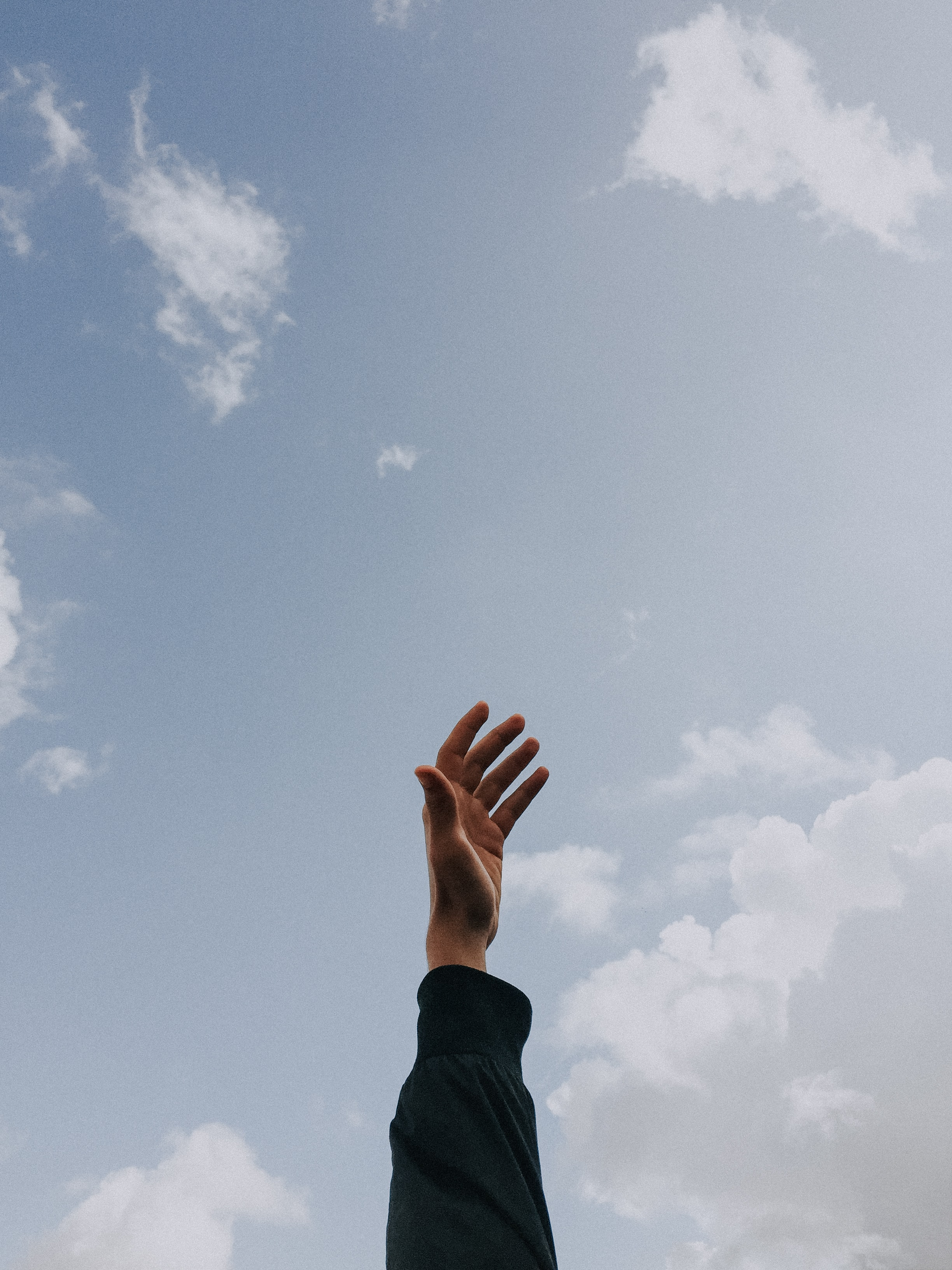 person raising left hand under cloudy sky at daytime