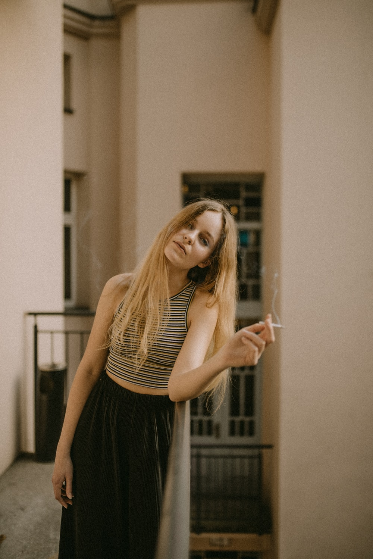 woman holding white cigarette