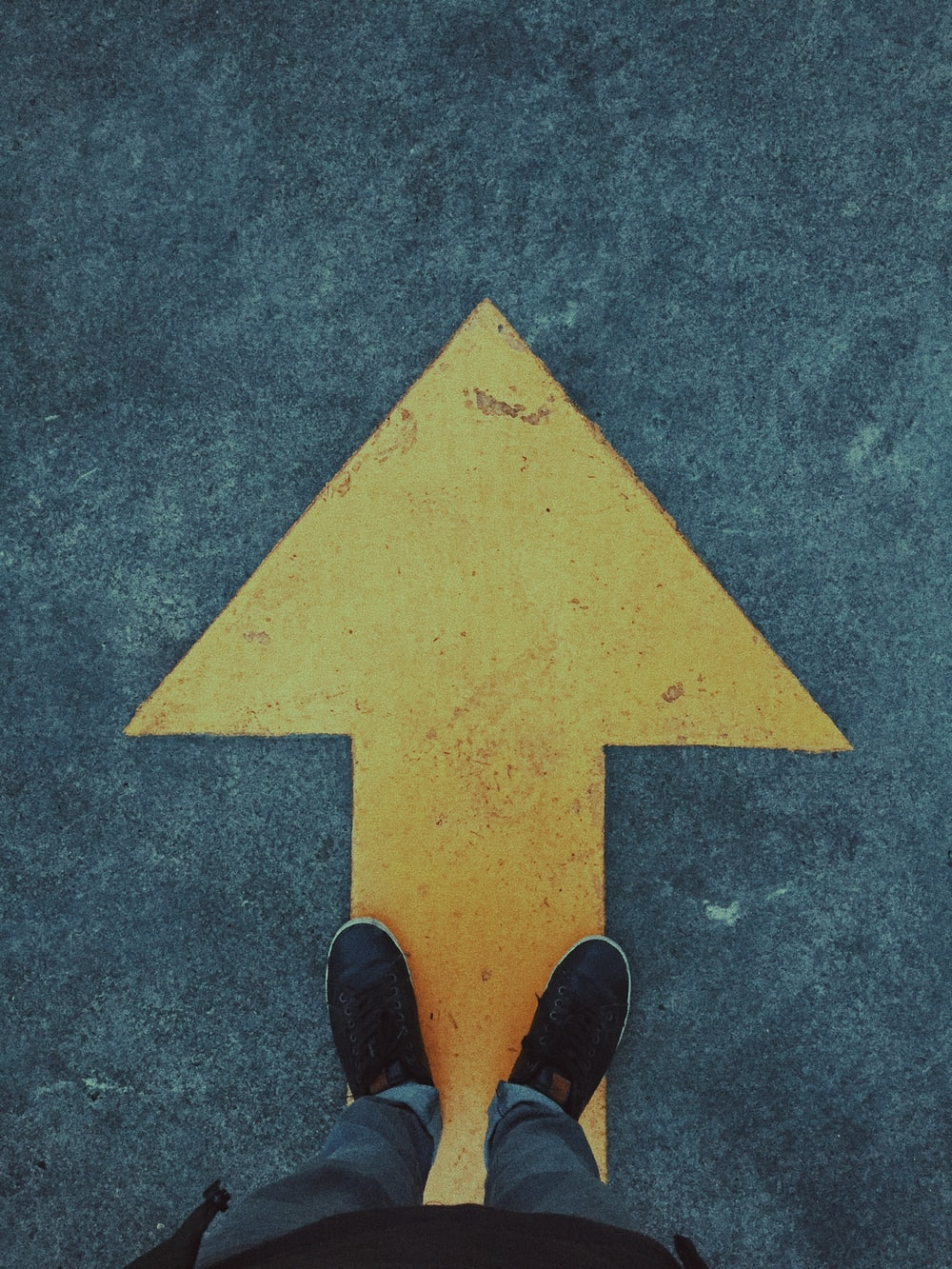 person standing on yellow arrow