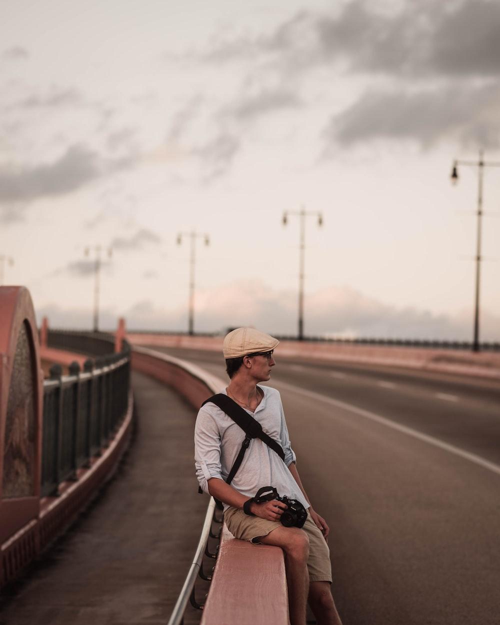 man wearing grey polo shirt sitting on road railings during daytime