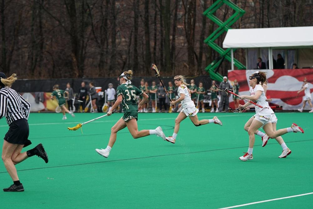 four women running on field