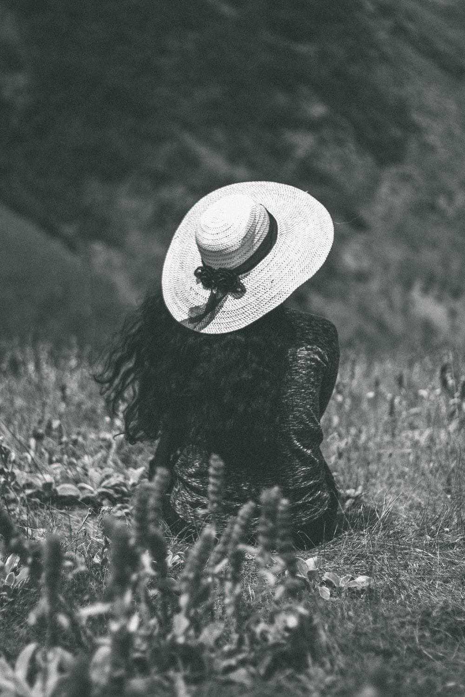 woman sitting on ground wearing sunhat