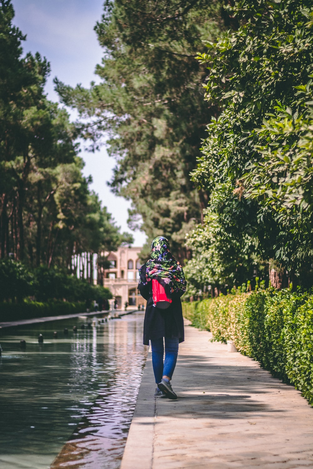 woman in black top walking by hedge and body of water