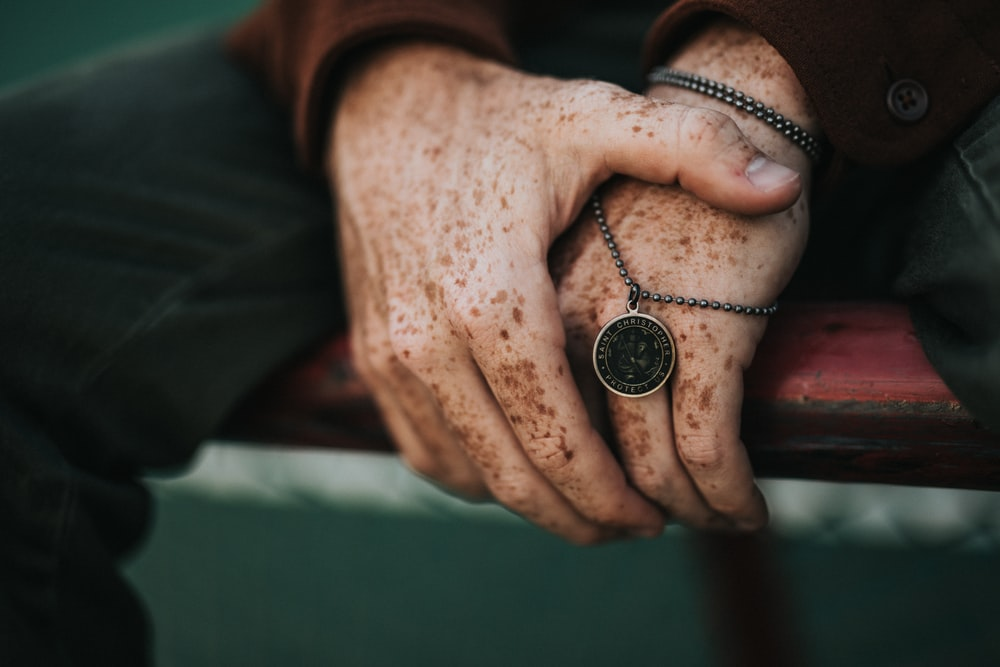 person holding round gold-colored necklace