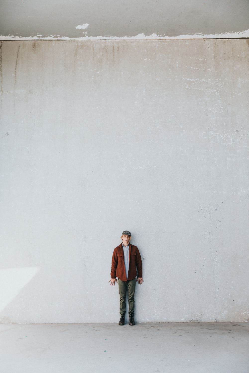 man in brown coat standing by the white wall