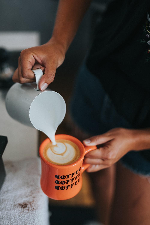 person pouring coffee on orange mug