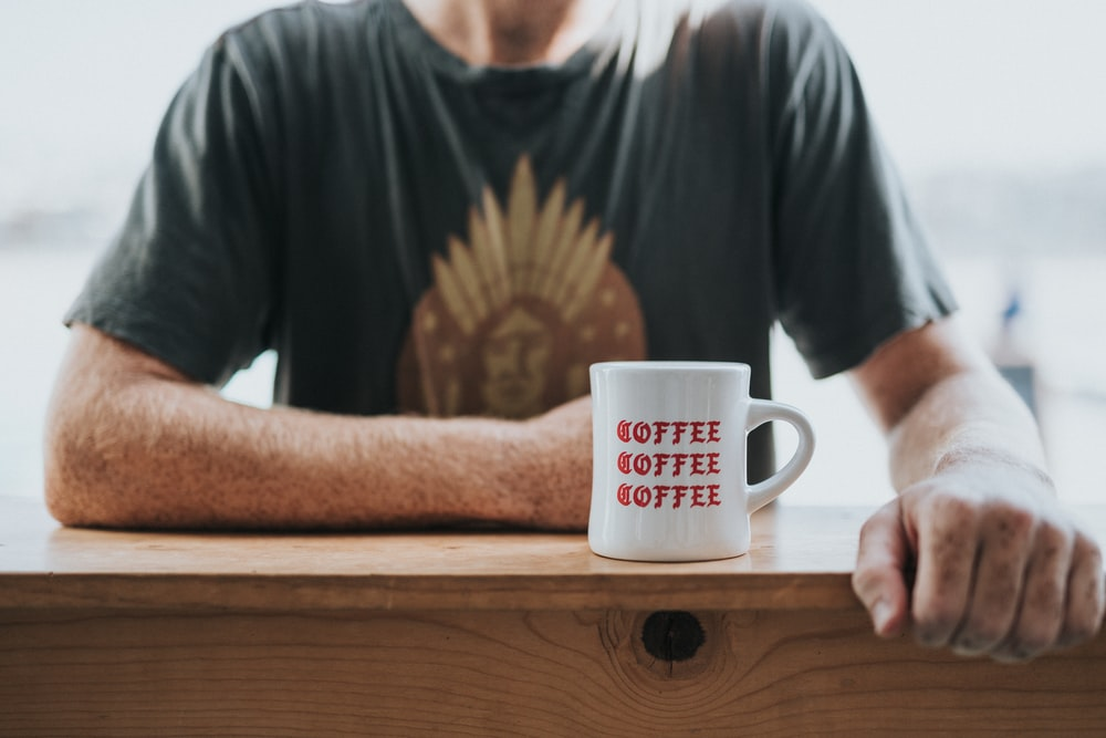 man in green and brown t-shirt sitting by the bar table with white coffee mug