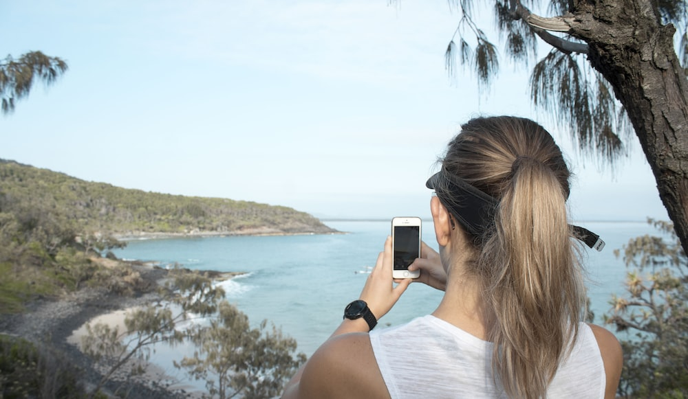 woman taking picture of blue beach