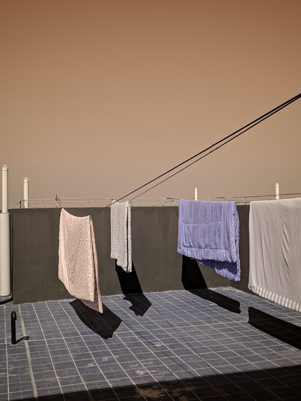 white towel near white blanket hanging near wall