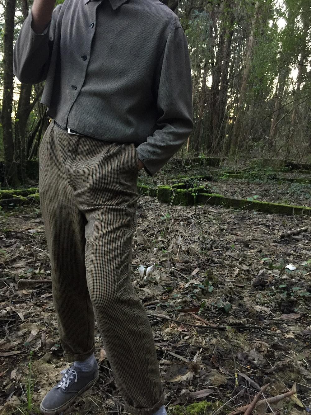 person wearing grey dress shirt and brown pants