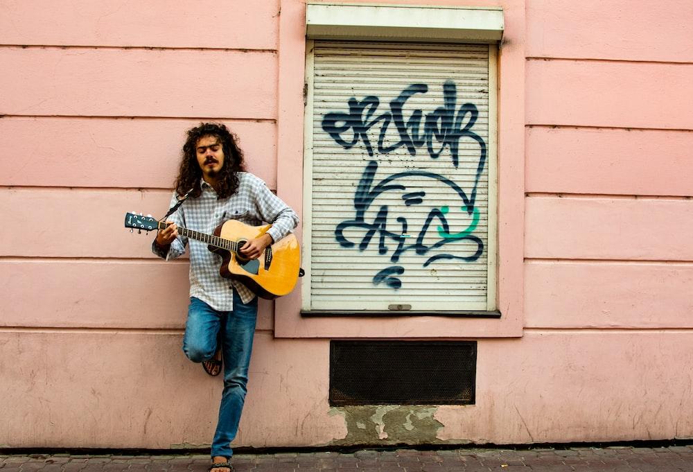 man playing guitar on street during daytime