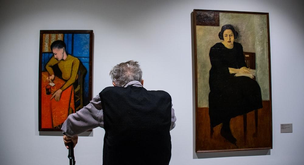 man looking at painting galleries