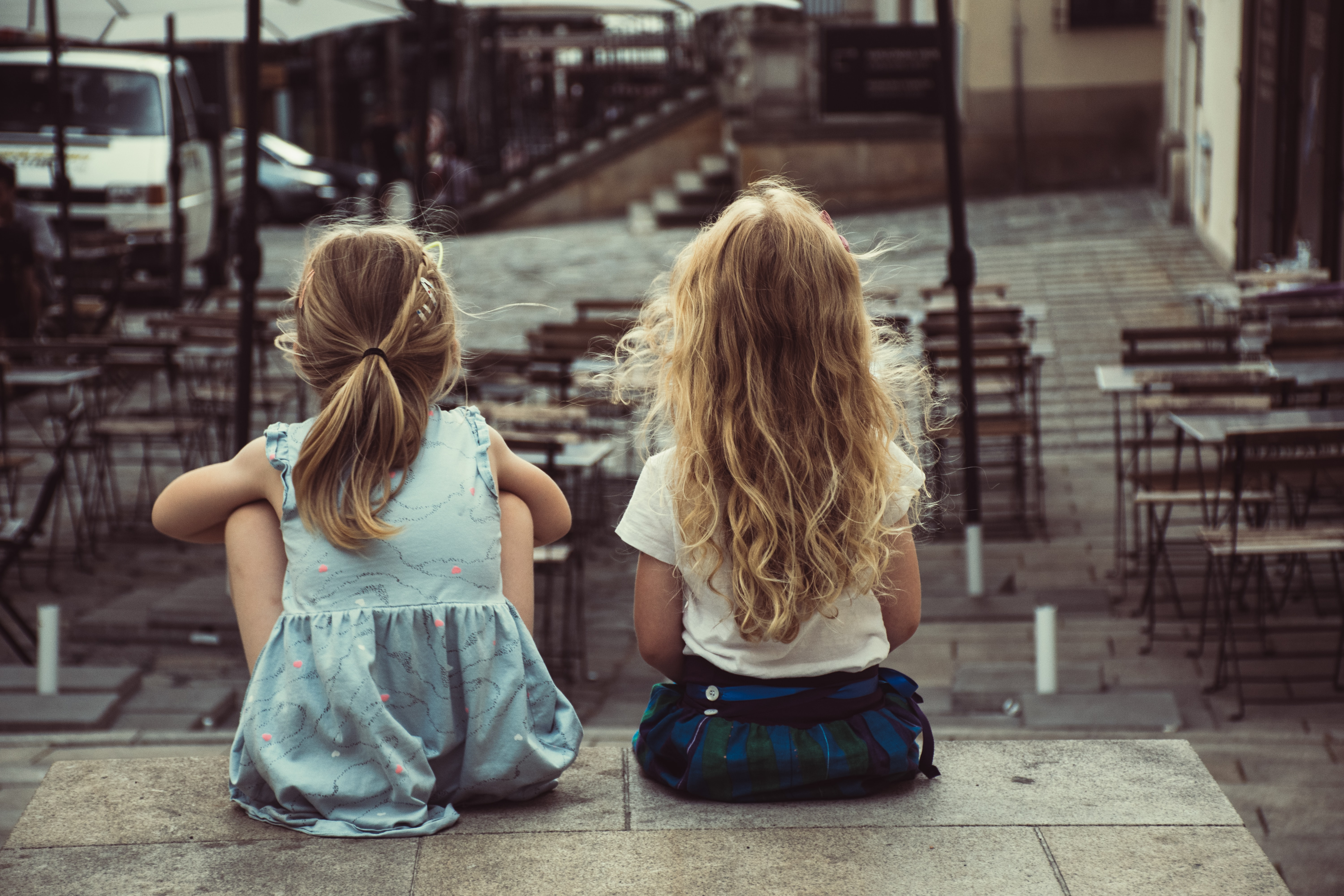 two girls sitting on concrete pavement facing on dining tables during daytime