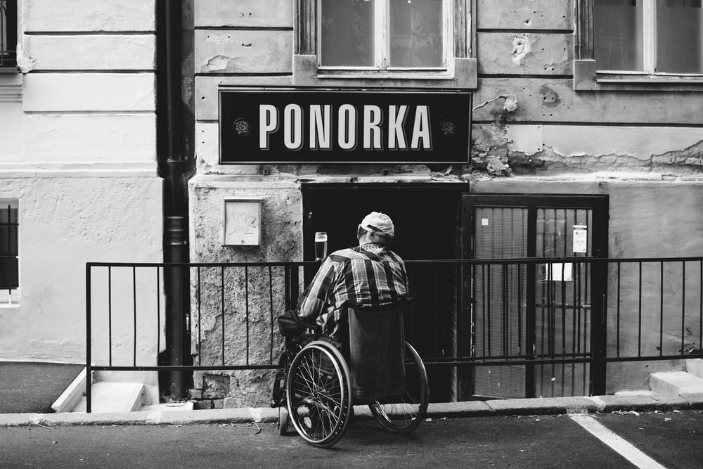 grayscale photography of person with wheelchair looking at Ponorka signage
