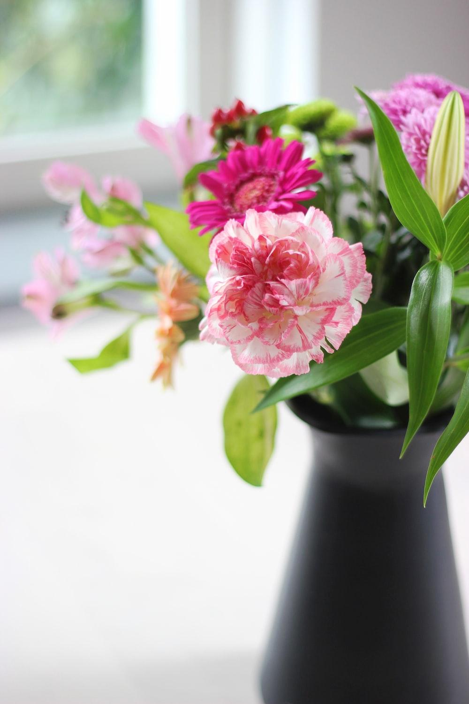 flowers in black vase on white surface