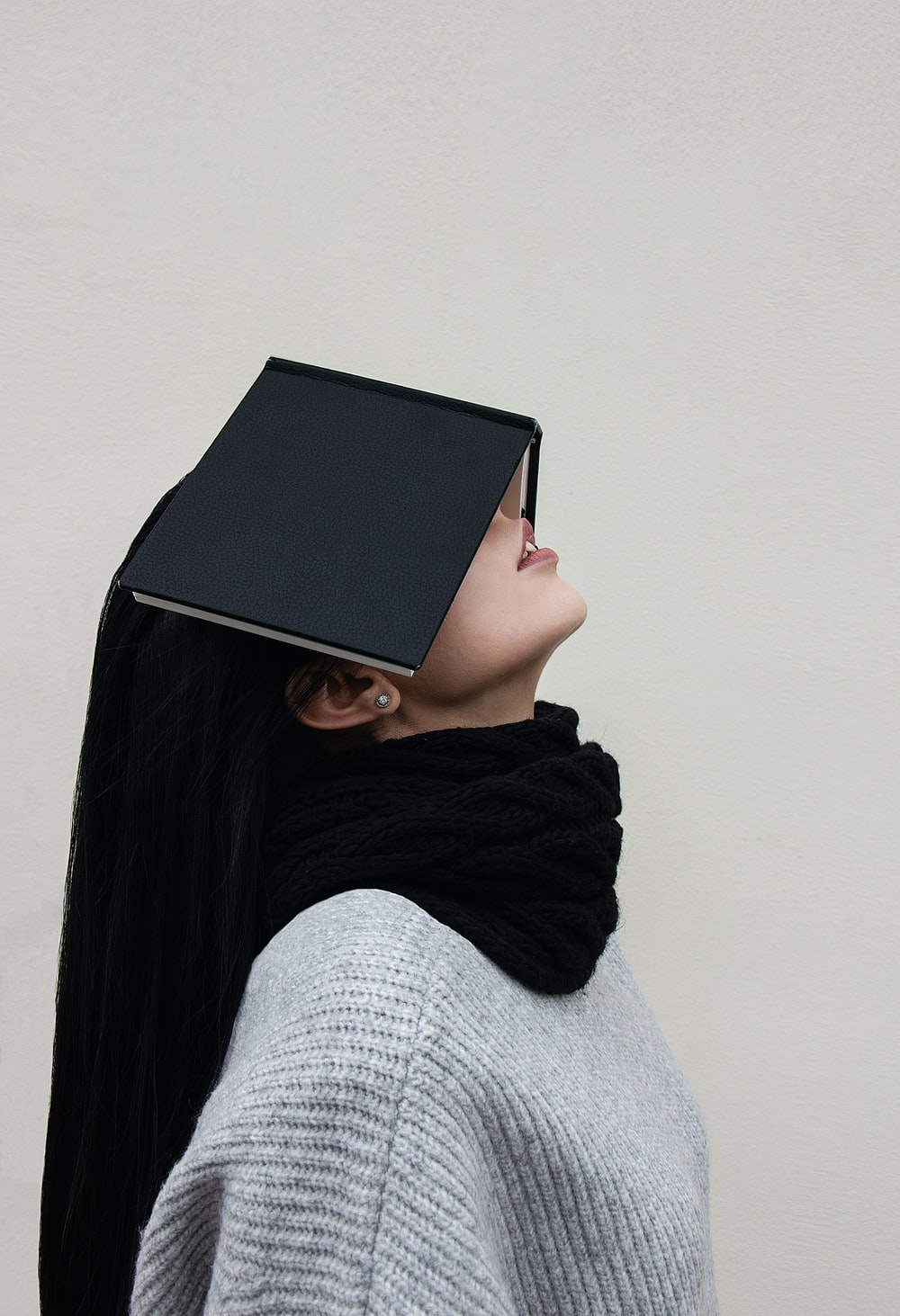 woman in gray sweater and black scarf covering face with black book