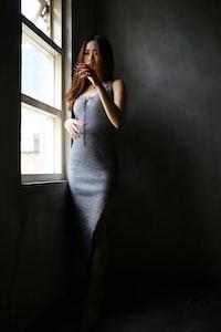 woman in gray dress standing beside window